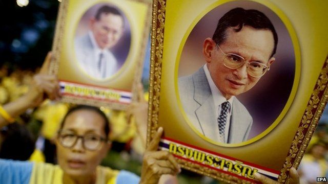 Thai well-wishers sing while holding up portraits of Thai King Bhumibol Adulyadej