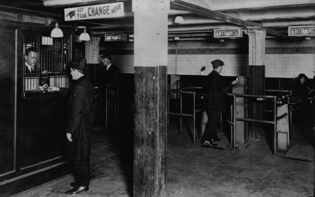 Un hombre billetes por monedas para pasar la barrera del metro de Nueva York en la década de 1920