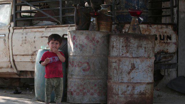 A boy stands near a car in Aleppo, Syria