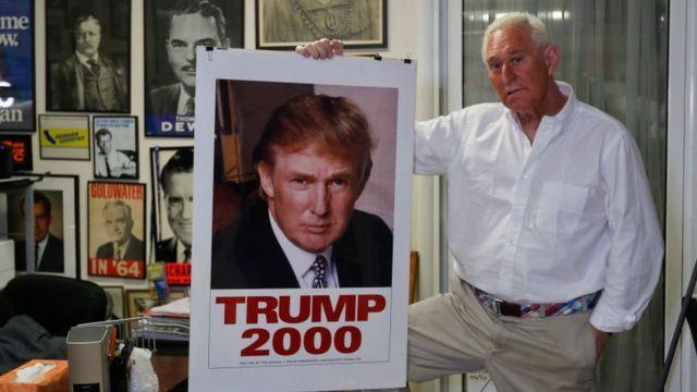 Roger Stone segurando um poster da campanha de Trump em 2000