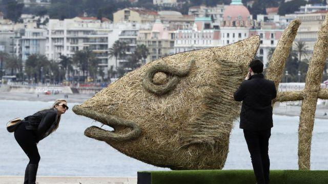 Woman dey kiss sculpture fish