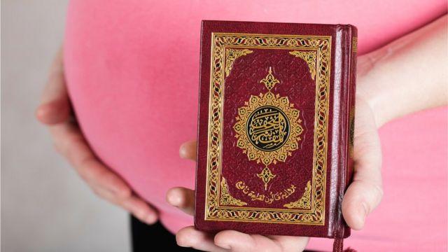 Una mujer embarazada con el Corán