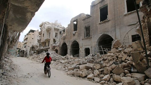 A boy rides a bicycle near damaged buildings in the rebel held area of Old Aleppo, Syria May 5, 2016