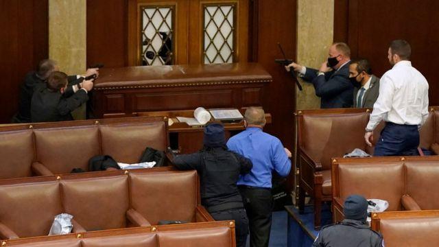 Співробітники правоохоронних органів направляють зброю на демонстрантів, які намагаються прорватися в зал засідань конгресу
