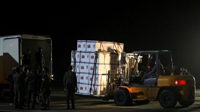 Lotes de doses da vacina Coronavac são transportadas em caixas e levadas para um caminhão