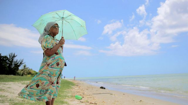 Señora chagosiana frente al mar mirando al horizonte con una sombrilla para protegerse del sol