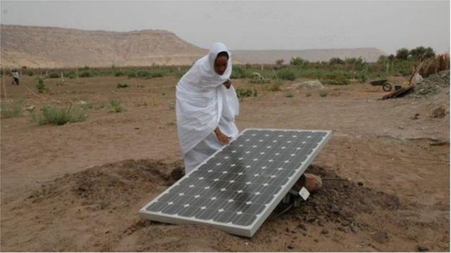 Жінка з сонячною батареєю в Африці у пустелі