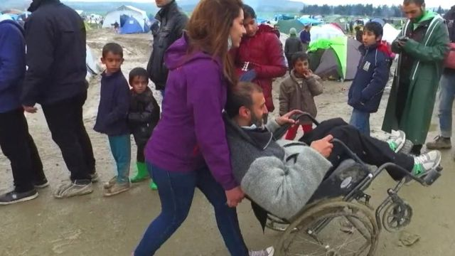 A Syrian refugee being pushed in a wheel chair in Idomeni, Greece.