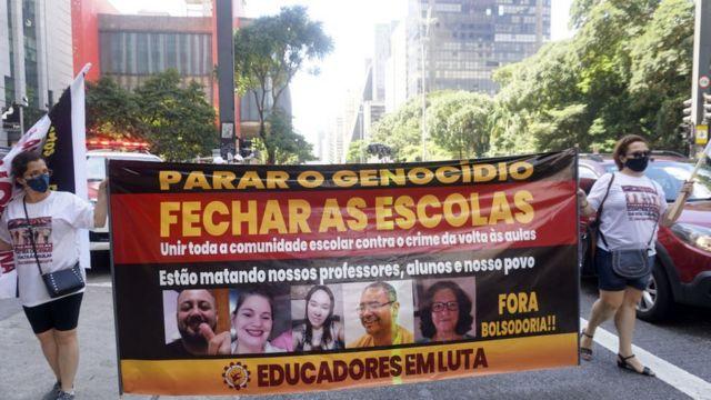 Duas mulheres seguram faixa na Avenida Paulista, em São Paulo, durante ato contra o retorno das aulas presenciais