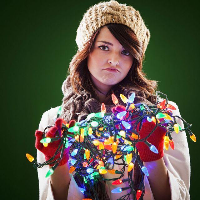 chica con luces de navidad enredadas