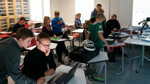 Sala de aula com professores sentados nas carteiras e estudantes em volta deles, dando aulas