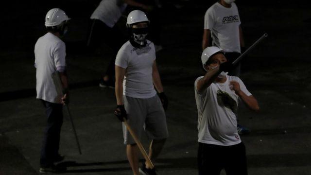白衣施暴者手持棍棒等武器。