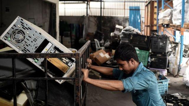 Homem em usina de reciclagem de eletrônicos