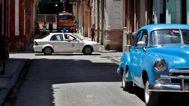 Un auto patrulla de la policía y un auto azul