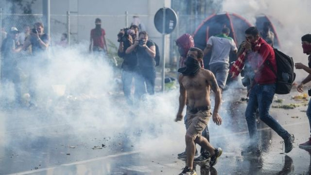 Hungarian police use tear gas at the border crossing into Hungary, near Horgos, Serbia, Wednesday, Sept. 16, 2015