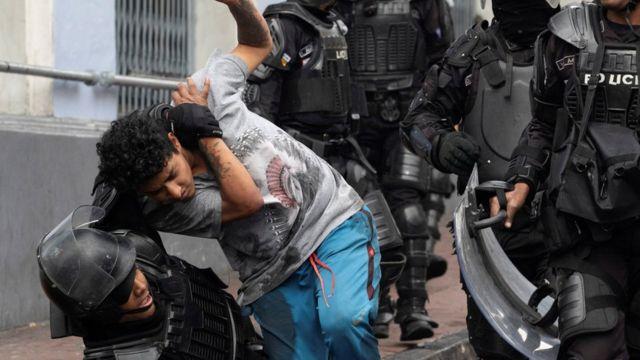 Un chico es agarrado por la policía antidisturbios