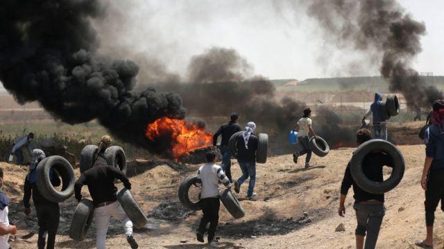 فلسطينيون يضرمون النار في إطارات
