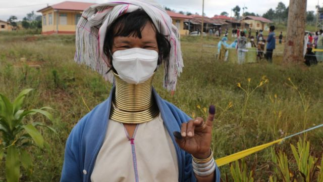An ethnic Kayan woman shows her inked finger after voting at a polling station in Myanmar on November 8, 2020.