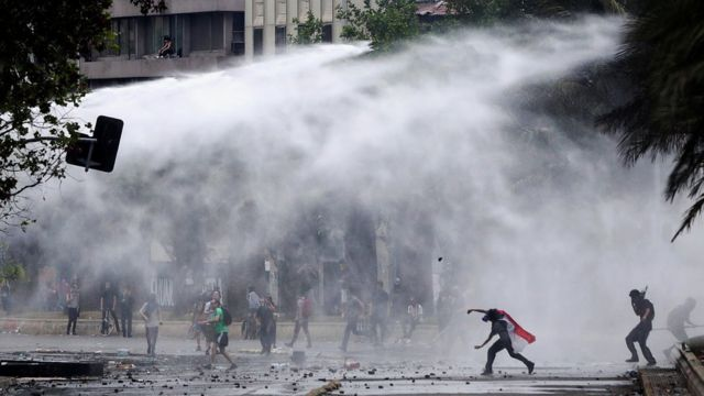 Riot police fire water cannons as they clash with demonstrators during a protest against Chile's state economic model in Santiago