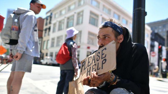 Un hombre sin hogar pide ayuda en una calle en San Francisco.