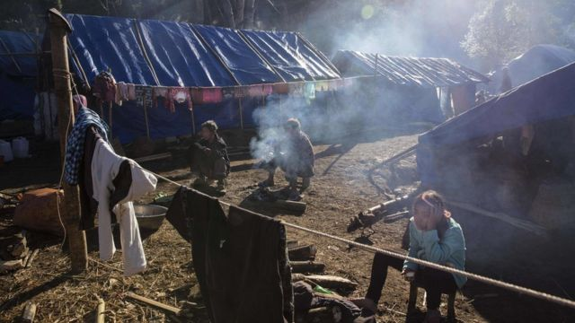 This photo is taken on January 21, 2017 shows refugees in front of their temporary shelter near Lung Byeng village, Waimaw township in Kachin state