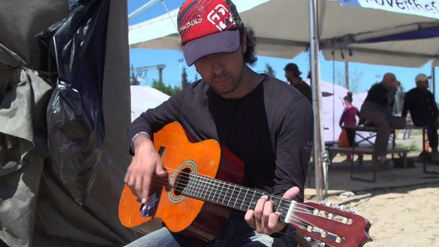 Samih playing a guitar in the Idomeni migrant camp.