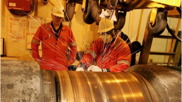Dos hombres trabajan en un gasoducto en Noruega.