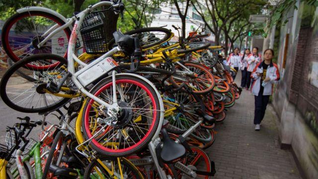 """南京碑亭巷內,各種顏色的共享單車堆放在一起,色彩交織的""""疊羅漢""""。"""