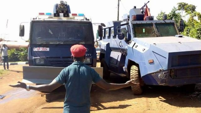 Uganda music star Bobi Wine dey stand in front of two armoured vehicle