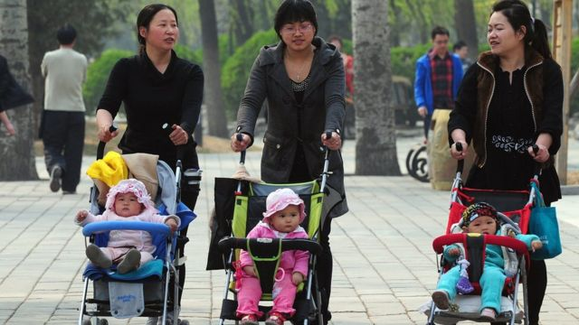 Three Chinese mothers walk with their children in prams