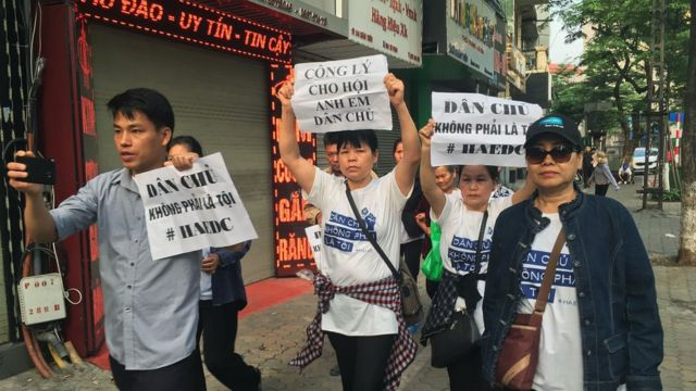 プラカードを持ったデモ参加者が、ハノイの裁判所に向かって行進した