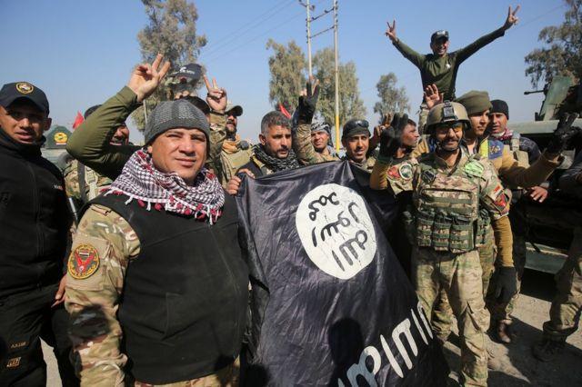 جنود عراقيون يحتفلون بإنزال علم تنظيم الدولة الإسلامية بعد السيطرة على المطار