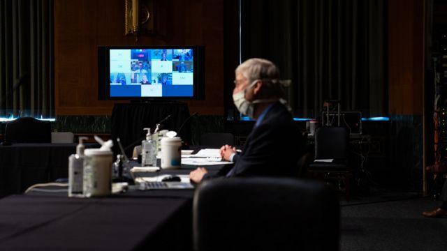 Una mujer en una gran sala con un monitor al fondo