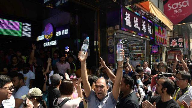 少數族群市民周日的遊行期間,在重慶大廈大門向參加遊行途經的人士派發瓶裝水。