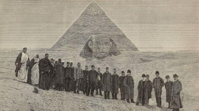 Foto antiga mostra homens posando em frente à pirâmide do Egito