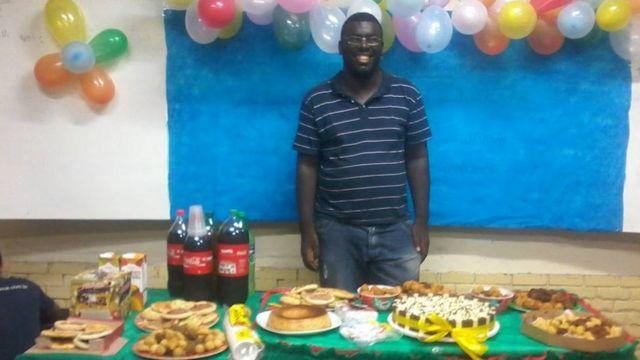 Thiago dos Santos Conceição sorri em mesa de comemoração de aniversário