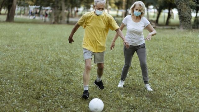 Homem e mulher de máscara jogam futebol