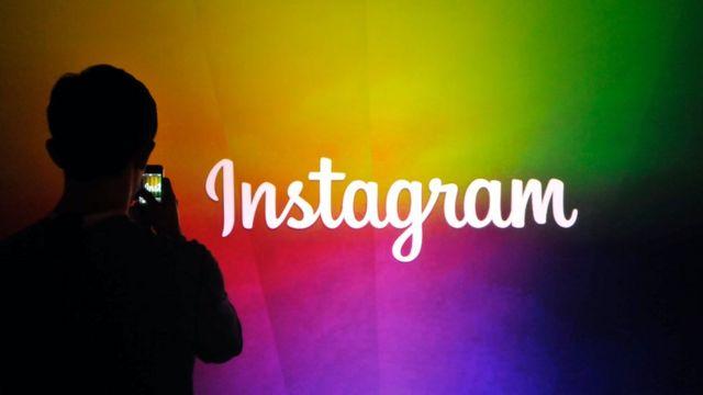 Una persona tomando una foto del logo de Instagram