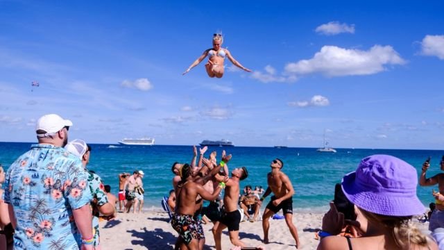 A group of young people throws a girl in the air in Miami Beach