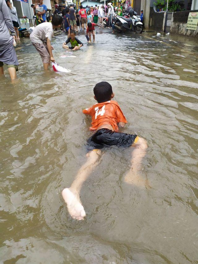 Anak-anak terlihat asik berenang saat hujan mengenangi Jakarta.