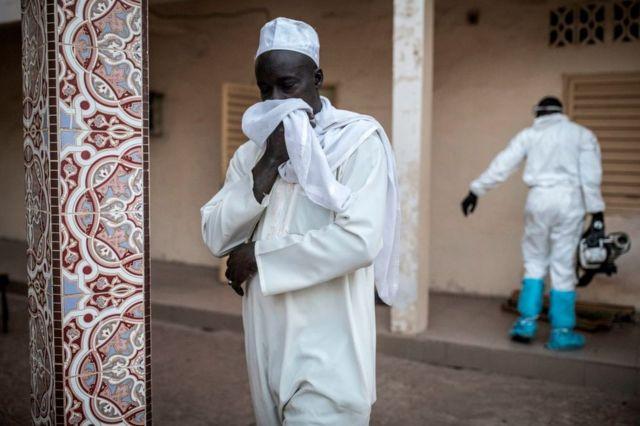 Un hombre se tapa la boca con un pañuelo mientras otro desinfecta una mezquita en Dakar, Senegal, como medida preventiva contra el coronavirus, el 1 de abril de 2020.