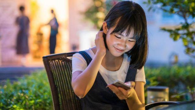 مراهقة صينية تستخدم الهاتف