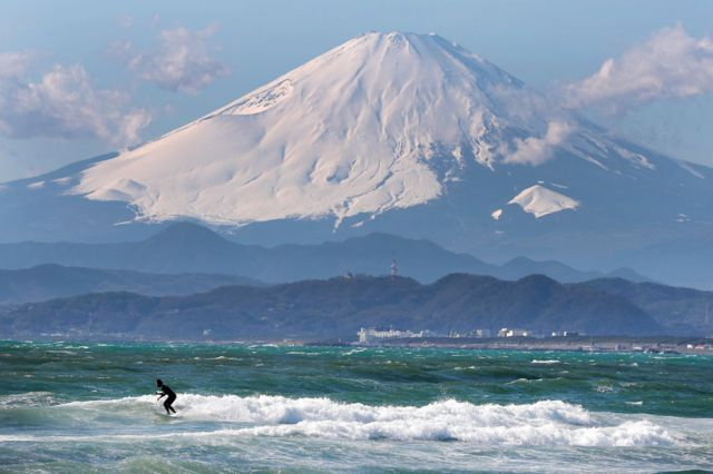 Mount Fuji and a surfer.