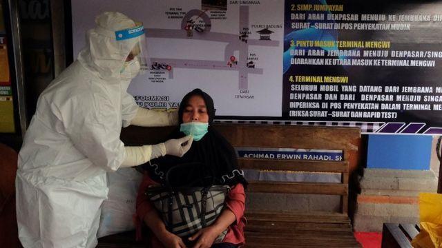 Petugas kesehatan mengambil sampel tes cepat antigen dari seorang penumpang bus di Terminal Tipe A Mengwi, Badung, Bali, Selasa (04/05)
