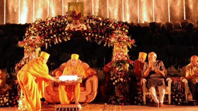 BAPSના તત્કાલીન વડા પ્રમુખ સ્વામી સાથે ગાંધીનગરના અક્ષરધામ મંદિરમાં યોજાયેલા એક કાર્યક્રમમાં નરેન્દ્ર મોદી, એ સમયે મોદી ગુજરાતના મુખ્યમંત્રી હતા