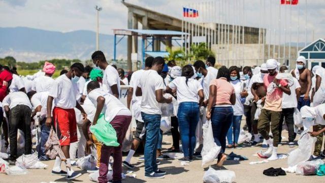 Pessoas buscam seus pertences em aeroporto haitiano