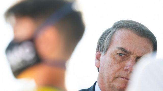 Bolsonaro olha para o lado, perto de apoiador com máscara de prevenção ao coronavírus