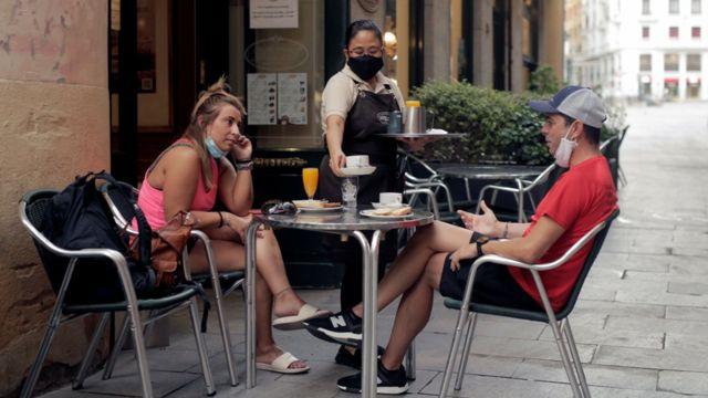 Duas pessoas tomam café da manhã em bar de Madrid, na Espanha