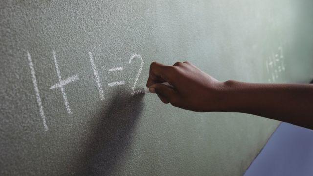 Pessoa escreve conta matemática no quadro de giz