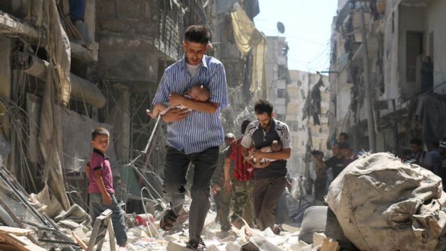 Syrian men carrying babies make their way through the rubble of destroyed buildings following a reported air strike on the rebel-held Salihin neighbourhood of the northern city of Aleppo, on September 11, 2016.
